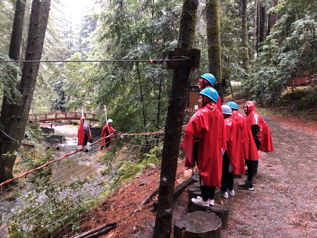 Students cheering on their peers as they finish the challenge course.