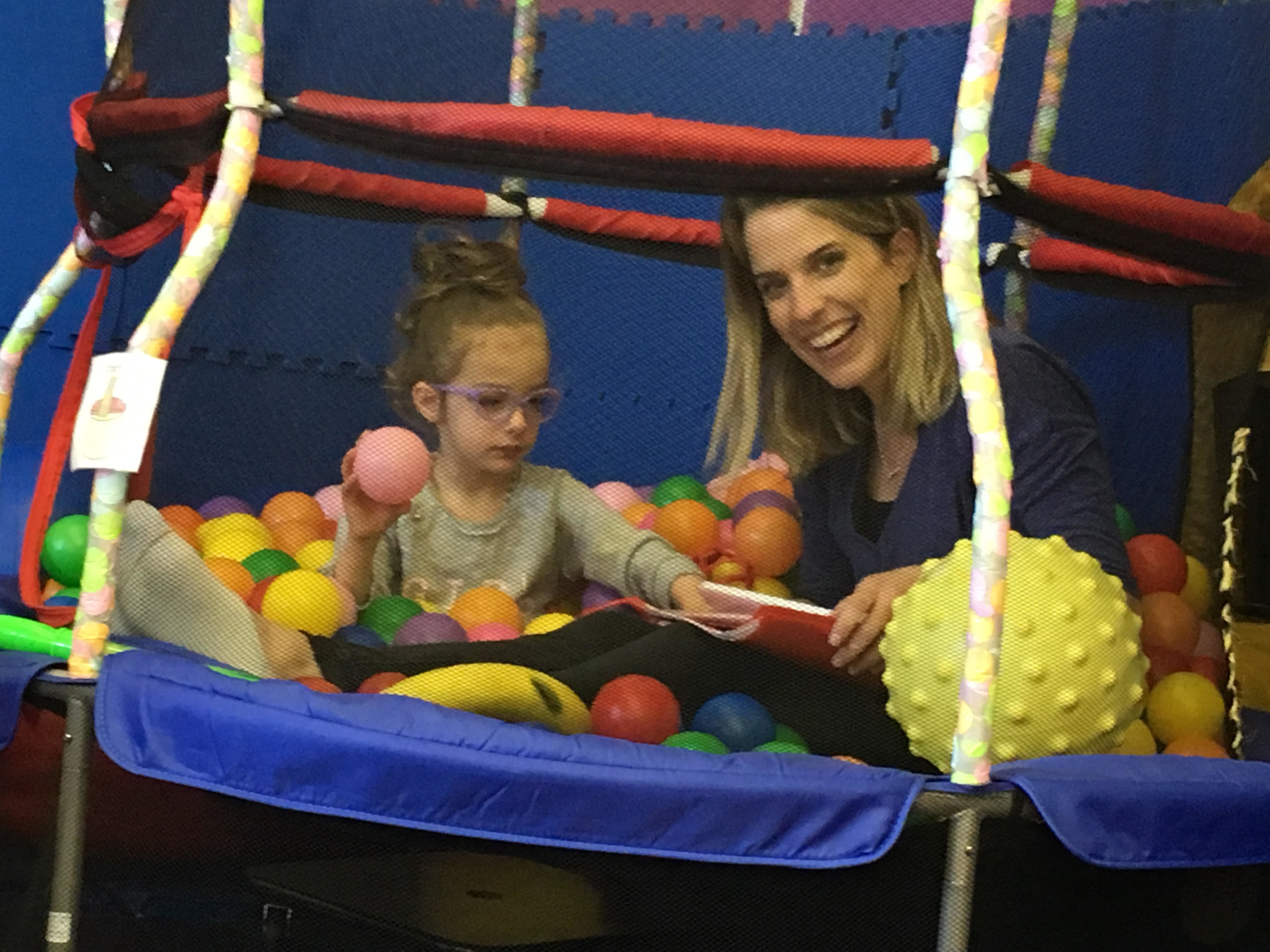 Speech teacher in ball pit with student